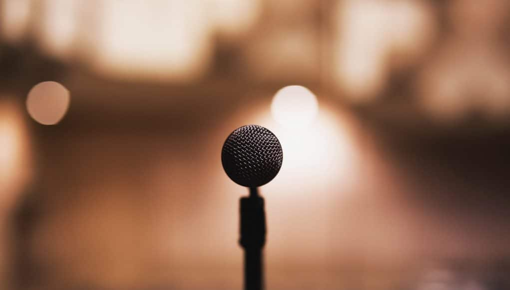 A public speaker uses his voice to capture his audience attention